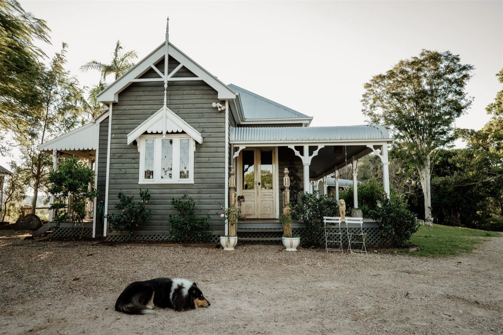 A black, long-haired dog lying in front of the main residence at Tooraloo Farm, showing that the property is pet-friendly.